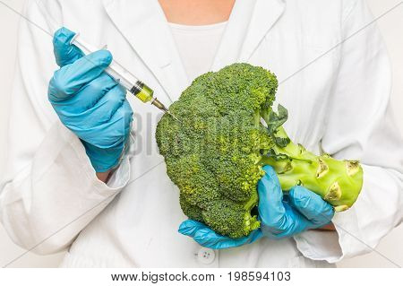 Gmo Scientist Injecting Liquid From Syringe Into Broccoli