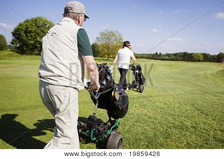 Active senior golf couple pushing golf trolley with bag on fairway on beautiful golf course with blue sky in background.
