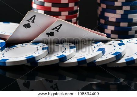 Two aces of playing cards lie on chips for playing poker on a dark background