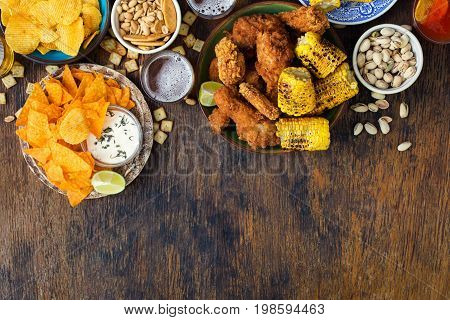 Fried chicken sauces beer potato chips nachos peanuts pistachios and crackers on a wooden table with border top view