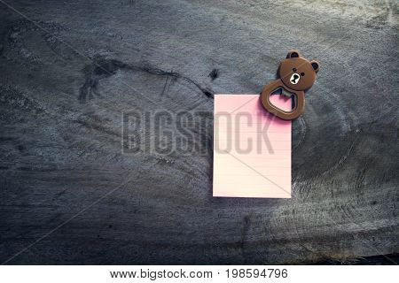 Empty paper sheet on Wood wall. Note paper with magnetic bear.