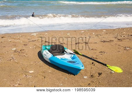 Concept of beach activity, water sport and kayaking. A bright blue kayak on the beach.