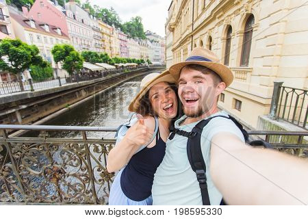 Happy romantic couple of tourists makes selfie self-portrait in Karlovy Vary while traveling across Europe