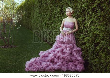 Woman in a magnificent dress is walking in the park.
