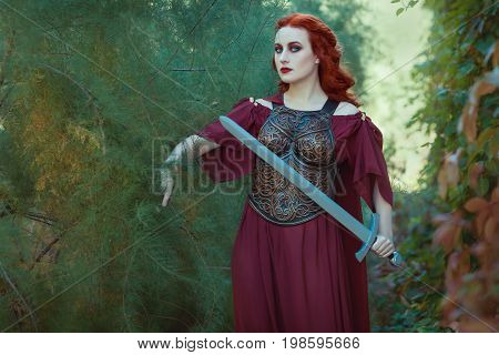 Red-haired woman warrior with a sword in her hand she's a defender.