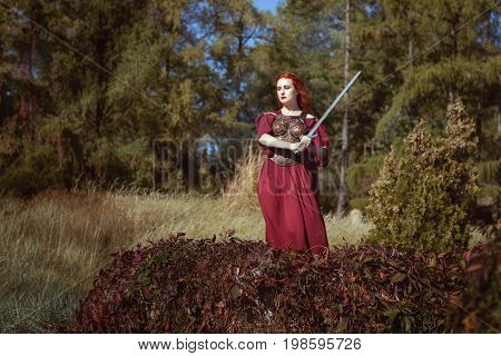 In the forest a woman with a sword she is a warrior and ready to defend.