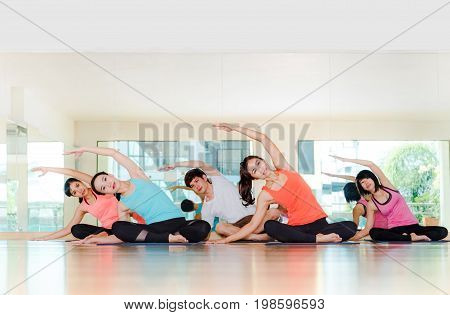 Yoga Class In Studio Room,group Of People Doing Seated Side Stretch Right Poses With Calm Relax Emot
