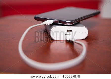 Cell Phone Charging With Power Bank on wooden table