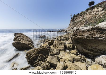Rugged rocky shoreline with motion blur water in Rancho Palos Verdes near Los Angeles, California.