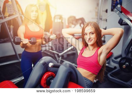 Close-up of a young girl in a sports hall shakes a press sit-ups on a sports simulator, in the background a girl is doing exercises. Concept group sports, girlfriends train.