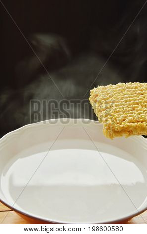 instant noodles floating on hot water in bowl