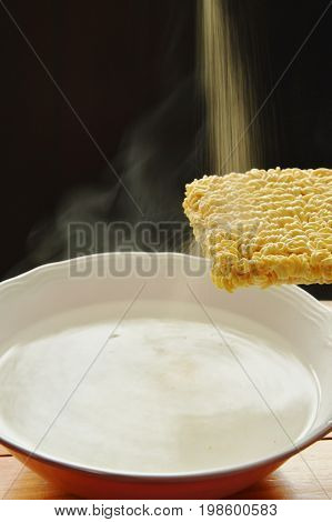 instant noodles floating on hot water in bowl and dressing seasoning powder