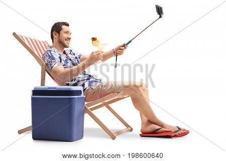 Tourist with a cocktail sitting in a deck chair next to a cooling box and taking a selfie isolated on white background