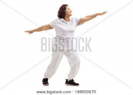 Full length profile shot of an elderly woman practicing yoga isolated on white background