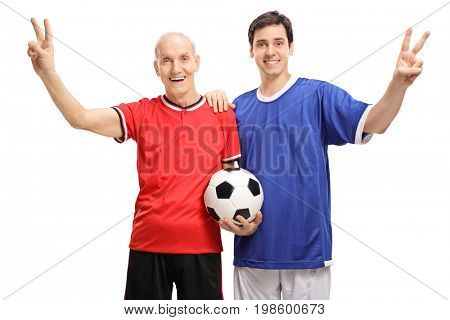 Senior and a young man dressed in jerseys holding a football and making victory signs isolated on white background