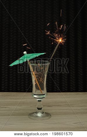 A cocktail umbrella with a sparkler in a cocktail glass
