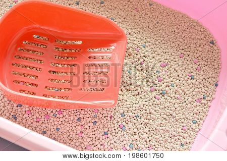 red plastic shovel on cat litter in pink box