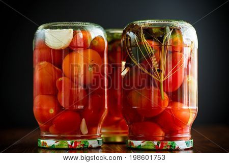 Home preservation. Canned in a glass jar ripe tomatoes on a wooden table.