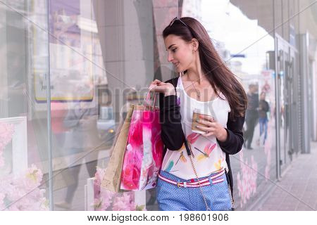 Cutie young girl with bags in hands at the shopping center
