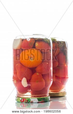 Home preservation. Canned in a glass jar ripe tomatoes on a white background. .