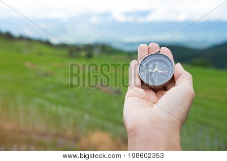 Compass In The Hand With Rice Field On Terrace Nature Background. Journey, Trip, Travel