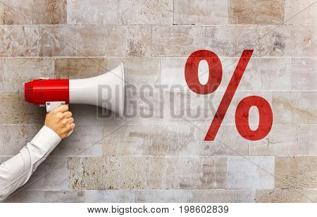 Sale Concept - Megaphone in hand yelling on red percentage sign on stone background