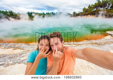 Funny selfie couple tourists at New Zealand pools travel. Young people doing goofy face at smell bad sulfur smell at colorful geothermal hot springs ponds, waiotapu.