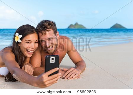 Beach vacation couple taking fun phone selfie on Hawaii vacation. Asian girl Caucasian man relaxing on Lanikai beach, Oahu, on summer holidays using smartphone for pictures together.