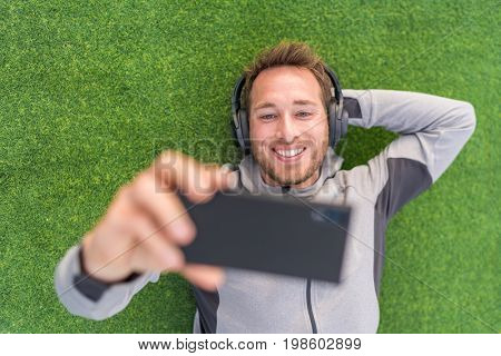 Happy man watching phone video app listening with headphones and smartphone relaxing outside on summer green grass.