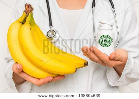 Female Doctor Compare Pile Of Pills With Fresh Banana