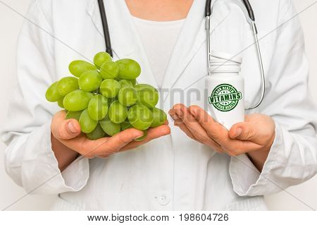 Female Doctor Compare Pile Of Pills With Fresh Grapes