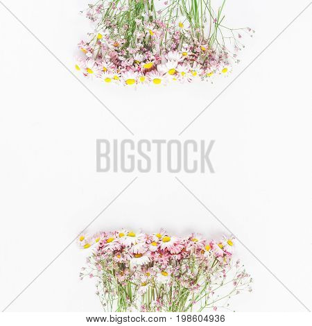 Flowers composition. Floral frame made of pink gypsophila flowers and daisy flowers on white background. Flat lay top view copy space square