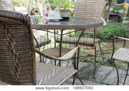 Wicker Rattan Chair And Table On Patio In Garden