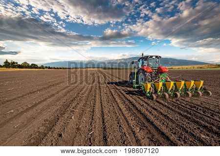 Varna, Bulagria - April 01, 2017. Big Steyr tractor with attached Great Plains seeder for sunflower seeds. Agriculture tractor sowing seeds and cultivating field.