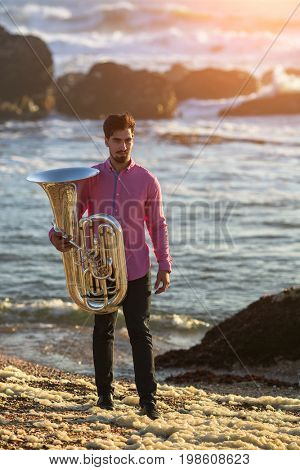 Musician with trumpet on the sea coast during surf. Tuba instrument.