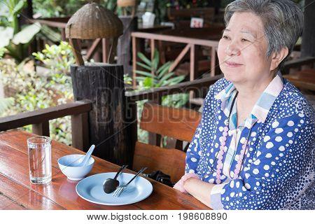 Elder Senoir Waiting For Food. Happy Elderly Woman Sitting At Restaurant.