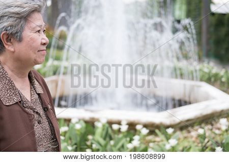 Asian Elder Woman Standing Near Fountain In Garden. Elderly Senior Female Resting And Relaxing In Pa