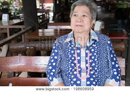 Elder Senoir Waiting For Food. Happy Elderly Woman Sitting At Restaurant.