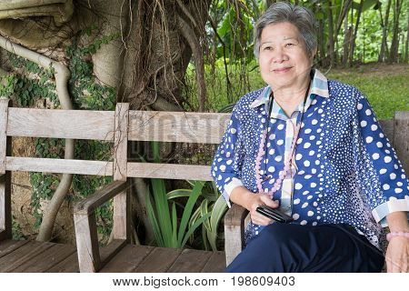 Asian Elder Woman Holding Mobile Smart Phone While Sitting On Chair In Garden. Elderly Senior Female