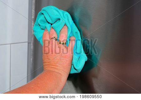 Housework wipe off dust and dirt with blue rags. Stainless steel surface clean and polish in the household.