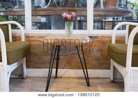Pink Siam Tulip Flower In Vase On Wood Table, White Rattan Wicker Chair Near Window. Decoration And