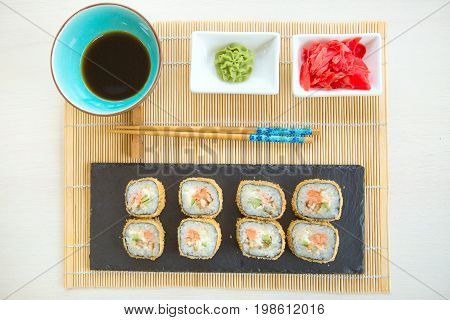 Sushi Rolls On Black Slate Surface. Japanese Food. Hot Fried Sushi Roll