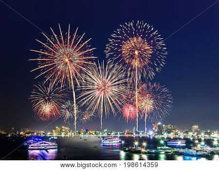 Fireworks over cityscape by the beach and sea surrounding with hotels restaurant and service boats and cruises during blue twilight time for celebrating New Year eve and special occasion on holidays