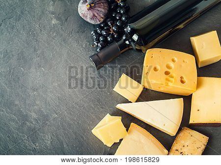 Different types of cheeses, red wine, grapes and figa on black board, top view