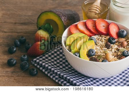 Muesli or granola on white bowl with fresh fruits nuts and cereal. Granola top with blueberries strawberries and avocado served with milk and honey for breakfast.Granola is healthy food for dieting. Muesli or granola on wood table.