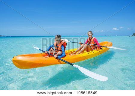 Two happy boy and girl kayaking at tropical sea on yellow kayak