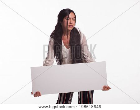 Young pensive woman portrait of a confident businesswoman showing presentation, pointing placard gray background. Ideal for banners, registration forms, presentation, landings, presenting concept.