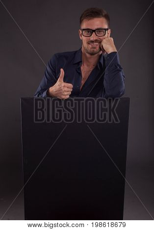 Young happy man portrait of a confident businessman showing presentation, pointing paper placard black background. Ideal for banners, registration forms, presentation, landings, presenting concept.