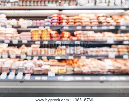 Defocused blur of supermarket shelves with sausages. Blur background with bokeh. Defocused image