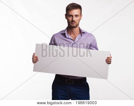 Young serious man portrait of a confident businessman showing presentation, pointing paper placard gray background. Ideal for banners, registration forms, presentation, landings, presenting concept.